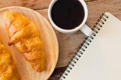 Carnet de café de croissants sur la table en bois - modifiez la tonalité le vintage photo stock