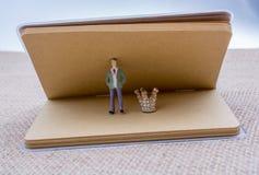 Carnet de figurine et couronne d'or de couleur image libre de droits