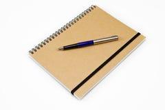 Carnet de notes à spirale de Brown avec le stylo-plume Photographie stock libre de droits