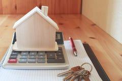 Carnet de papier avec la calculatrice, le modèle de maison, les clés et le stylo sur la table en bois photographie stock libre de droits