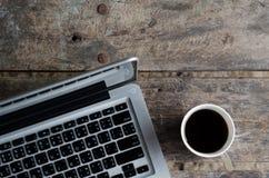 Carnet en aluminium (ordinateur portable) avec la tasse de café chaud sur la table en bois Image stock