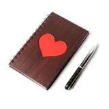 Carnet en bois de texture avec le coeur rouge et stylo sur le fond blanc Photo libre de droits
