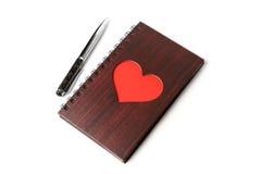 Carnet en bois de texture avec le coeur rouge et stylo sur le fond blanc Photos libres de droits