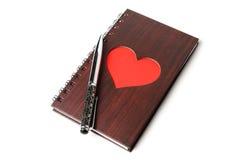 Carnet en bois de texture avec le coeur rouge et stylo sur le fond blanc Images libres de droits