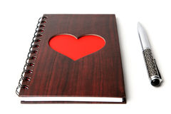 Carnet en bois de texture avec le coeur rouge et stylo sur le fond blanc Photographie stock libre de droits