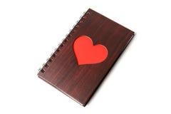 Carnet en bois de texture avec le coeur rouge sur le fond blanc Photographie stock