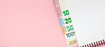 Carnet et argent sur la table Billets de banque de bloc-notes et d'euro sur un fond rose avec l'espace de copie Escroquerie de pl Image libre de droits