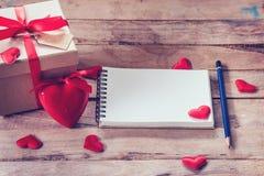 Carnet et boîte-cadeau vides avec le coeur rouge sur le fond en bois Image stock
