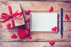 Carnet et boîte-cadeau vides avec le coeur rouge sur le fond en bois Photos stock