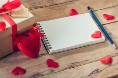Carnet et boîte-cadeau vides avec le coeur rouge sur le fond en bois Photo stock