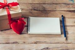 Carnet et boîte-cadeau vides avec le coeur rouge sur le fond en bois Photographie stock