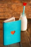 Carnet et bouteille de lait avec le coeur Images libres de droits