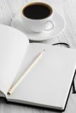 Carnet et café sur un fond blanc Photos stock
