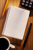 Carnet et calculatrice sur le bureau avec la tasse de café Image libre de droits