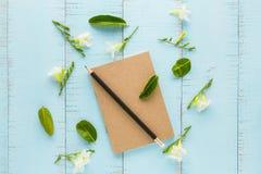 Carnet et crayon avec des fleurs Photographie stock libre de droits
