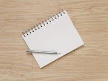 Carnet et crayon sur le plancher en bois Image libre de droits