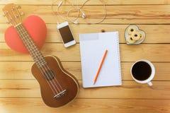 Carnet et crayon vides avec du café, le biscuit, le mobile et l'ukulel Photographie stock libre de droits