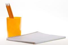 Carnet et crayons sur un fond blanc Images stock