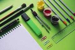 Carnet et diverses fournitures de bureau d'école sur la surface verte, de nouveau à l'école, bureau Photos stock