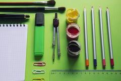 Carnet et diverses fournitures de bureau d'école sur la surface verte, de nouveau à l'école, bureau Images stock