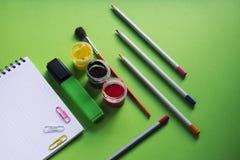 Carnet et diverses fournitures de bureau d'école sur la surface verte, de nouveau à l'école, bureau Image stock