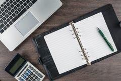 Carnet et stylo avec la calculatrice sur le bureau Photographie stock libre de droits