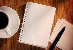 Carnet et stylo avec la tasse de café sur le bureau Photo stock