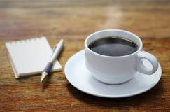 Carnet et stylo de tasse de café sur la table en bois Image stock