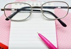 Carnet et verres roses de stylo Photo libre de droits