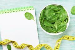 Carnet, feuilles vertes d'épinards et ruban métrique sur la vue supérieure en bois de table Régime et nourriture saine photographie stock libre de droits