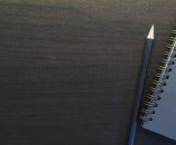 Carnet noir avec le crayon sur le fond de tableau Photos stock