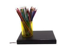 Carnet noir avec le verre du crayon d'isolement sur le fond blanc Photo stock