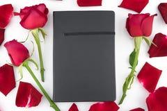 Carnet noir décoré des roses rouges et des pétales Image libre de droits