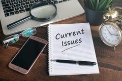 Carnet, ordinateur portable, smartphone, horloge et stylo avec le mot de QUESTIONS ACTUELLES sur un fond en bois photographie stock