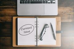 Carnet, ordinateur portable, stylo et lunettes sur une table en bois avec le mot de QUESTIONS ACTUELLES images libres de droits