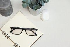Carnet ouvert avec les lunettes, les branches d'eucalyptus, la pierre et la bougie foncés sur le fond blanc images stock