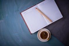 Carnet ouvert, crayon, tasse de thé, une tasse de café Fond foncé Photo libre de droits