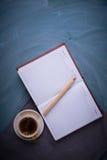 Carnet ouvert, crayon, tasse de thé, une tasse de café Fond foncé Image libre de droits