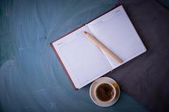 Carnet ouvert, crayon, tasse de thé, une tasse de café Fond foncé Photographie stock libre de droits