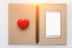 Carnet ouvert de blanc avec le coeur rouge et smartphone avec le spac de copie Photos libres de droits