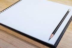 Carnet ouvert de plan rapproché avec le crayon Photographie stock libre de droits