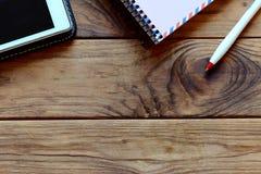 Carnet, PC de comprimé, stylo sur la table de bureau Fond en bois avec l'espace de copie pour le texte workspace Vue supérieure Image libre de droits