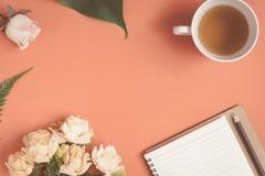 Carnet plat et rose de configuration placés sur un bureau rouge Photos stock