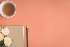 Carnet plat et rose de configuration placés sur un bureau rouge Image stock