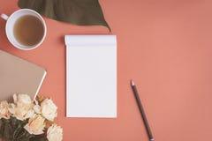 Carnet plat et rose de configuration placés sur un bureau rouge Image libre de droits