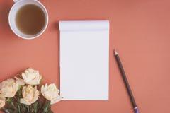 Carnet plat et rose de configuration placés sur un bureau rouge Photographie stock
