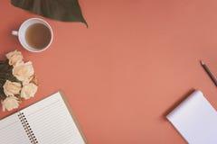 Carnet plat et rose de configuration placés sur un bureau rouge Images libres de droits