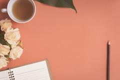 Carnet plat et rose de configuration placés sur un bureau rouge Photographie stock libre de droits
