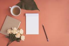 Carnet plat et rose de configuration placés sur un bureau rouge Photos libres de droits