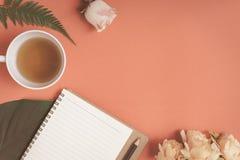Carnet plat et rose de configuration placés sur un bureau rouge Photo stock